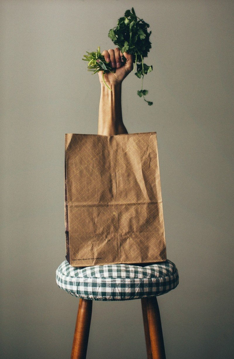 Stool With Paper Bag And Human Hand Holding Green Parsley